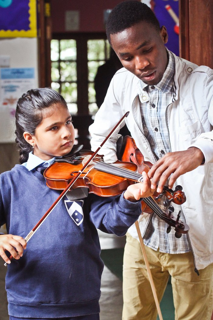 Child being taught the violin
